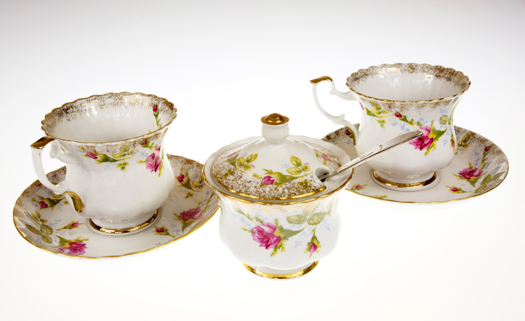 Two porcelain, decorative cups and sugar-bowl on isolated white background.Horizontal view.